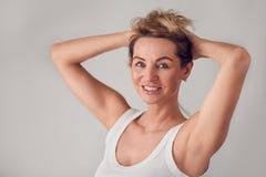 Attraktive blonde Frau, die ihr langes Haar hält Stockfoto
