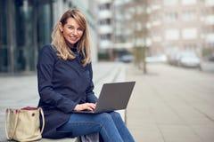 Attraktive blonde Frau, die ihren Laptop in der Stadt verwendet Stockbild