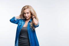 Attraktive blonde Frau, die mit den Händen im Haar aufwirft Lizenzfreie Stockbilder