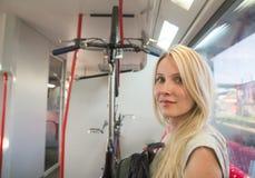 Attraktive blonde Frau, die mit ihrem Fahrrad reist Stockfotografie