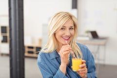 Attraktive blonde Frau, die Orangensaft trinkt Stockfoto