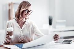 Attraktive blonde Frau, die Papierschale hält Stockbild