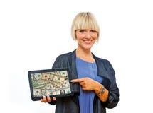 Attraktive blonde Frau, die Tablette mit Dollar auf Schirm hält Lizenzfreie Stockfotos