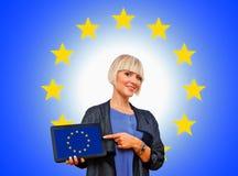 Attraktive blonde Frau, die Tablette mit europäischer Flagge hält Stockfotografie
