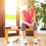 Attraktive blonde Frau erschöpft, stehend nach Turnhallentraining still Stockfoto