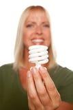 Attraktive blonde Frau hält energiesparende Leuchte an stockbilder