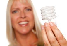 Attraktive blonde Frau hält energiesparenden Fühler an lizenzfreie stockfotos