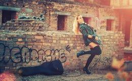 Attraktive blonde Frau im Anzug des schwarzen Körpers, in den dunklen Strümpfen, in der Lederjacke, die auf dem Dach des Altbaus  Stockfoto