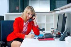 Attraktive blonde Frau im Büro sprechend mit Telefon Lizenzfreie Stockbilder