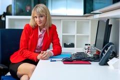 Attraktive blonde Frau im Bürositzen Stockfoto