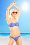 Attraktive blonde Frau im Bikini, tragende Sonnenbrille, auf Strand Lizenzfreies Stockbild