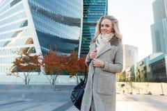 Attraktive blonde Frau im Herbstmantel, der im Geschäftsgebiet steht Lizenzfreie Stockfotografie