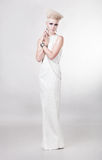Attraktive blonde Frau im langen weißen Kleid Stockbilder