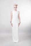 Attraktive blonde Frau im langen weißen Kleid mit dem kreativen Haar Stockfotos