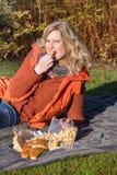 Attraktive blonde Frau im Park macht ein Picknick Stockfoto
