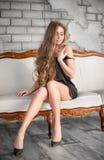Attraktive blonde Frau im schwarzen Kleid, das auf der Couch sitzt Lizenzfreie Stockbilder
