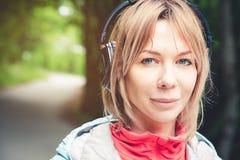 Attraktive blonde Frau im Waldnahaufnahmeporträt eines sportlichen lächelnden Mädchens, das Musik hört Stockbild