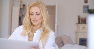 Attraktive blonde Frau im Weiß unter Verwendung ihres Laptops Lizenzfreies Stockfoto
