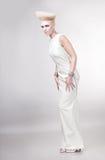 Attraktive blonde Frau im weißen Kleid mit dem kreativen Haar Lizenzfreies Stockfoto