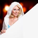 Attraktive blonde Frau im Winter kleidet mit einem Schild Lizenzfreie Stockfotos