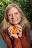 Attraktive blonde Frau ist mit Kürbis im Herbst froh Stockfotos