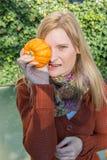 Attraktive blonde Frau ist mit Kürbis im Herbst froh Stockbild