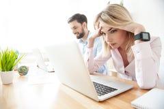 Attraktive blonde Frau ist von der Arbeit müde Lizenzfreie Stockbilder