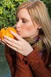 Attraktive blonde Frau küsst Kürbis im Herbst Lizenzfreies Stockfoto