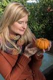 Attraktive blonde Frau küsst Kürbis im Herbst Stockbild