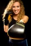 Attraktive blonde Frau locht mit Boxhandschuh Lizenzfreies Stockbild