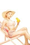 Attraktive blonde Frau mit dem Hut, der auf einem Sonnennichtstuer und -dr. sitzt Stockfoto