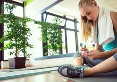 Attraktive blonde Frau mit dem intelligenten Telefon, stehend nach Turnhallentraining still Stockbild