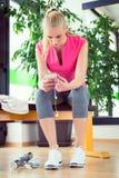 Attraktive blonde Frau mit dem intelligenten Telefon, stehend nach Turnhallentraining still Stockbilder