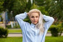Attraktive blonde Frau mit dem langen Haar im Park Stockfotos
