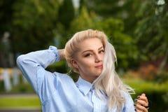 Attraktive blonde Frau mit dem langen Haar im Park Lizenzfreie Stockfotografie