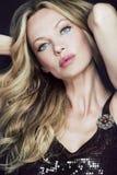 Attraktive blonde Frau mit dem langen lockigen Haar. Stockfotos
