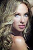 Attraktive blonde Frau mit dem langen lockigen Haar. Lizenzfreie Stockbilder
