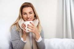 Attraktive blonde Frau mit einem reizenden freundlichen Lächeln Stockfoto