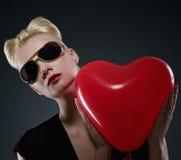 Attraktive blonde Frau mit einem roten Ballon. Stockfoto