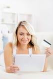Attraktive blonde Frau mit einer Kreditkarte und einem Tablet-Computer Stockfotos