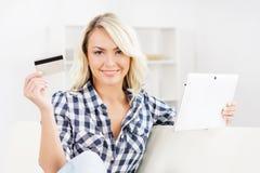 Attraktive blonde Frau mit einer Kreditkarte und einem Tablet-Computer Stockbild