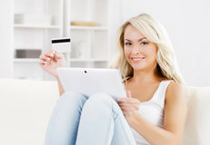 Attraktive blonde Frau mit einer Kreditkarte und einer Tablette Lizenzfreie Stockbilder
