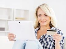 Attraktive blonde Frau mit einer Kreditkarte und einer Tablette Stockbilder