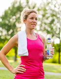 Attraktive blonde Frau mit einer Wasserflasche Stockbild