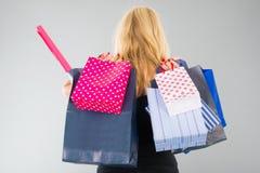 Attraktive blonde Frau mit Einkaufstaschen Stockbild