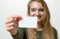 Attraktive blonde Frau mit ihrer Visitenkarte Lizenzfreies Stockfoto