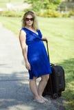Attraktive blonde Frau mit Koffer - Unfähigkeit Stockfoto