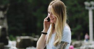Attraktive blonde Frau mit Tätowierung sprechend am Handy im Park auf Hintergrund des Brunnens stock footage