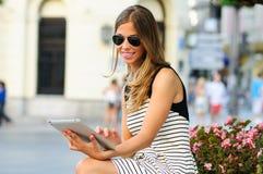Attraktive blonde Frau mit Tablettecomputer im städtischen Hintergrund Lizenzfreies Stockbild