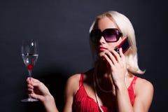 Attraktive blonde Frau mit Telefon und Glas Stockfotos